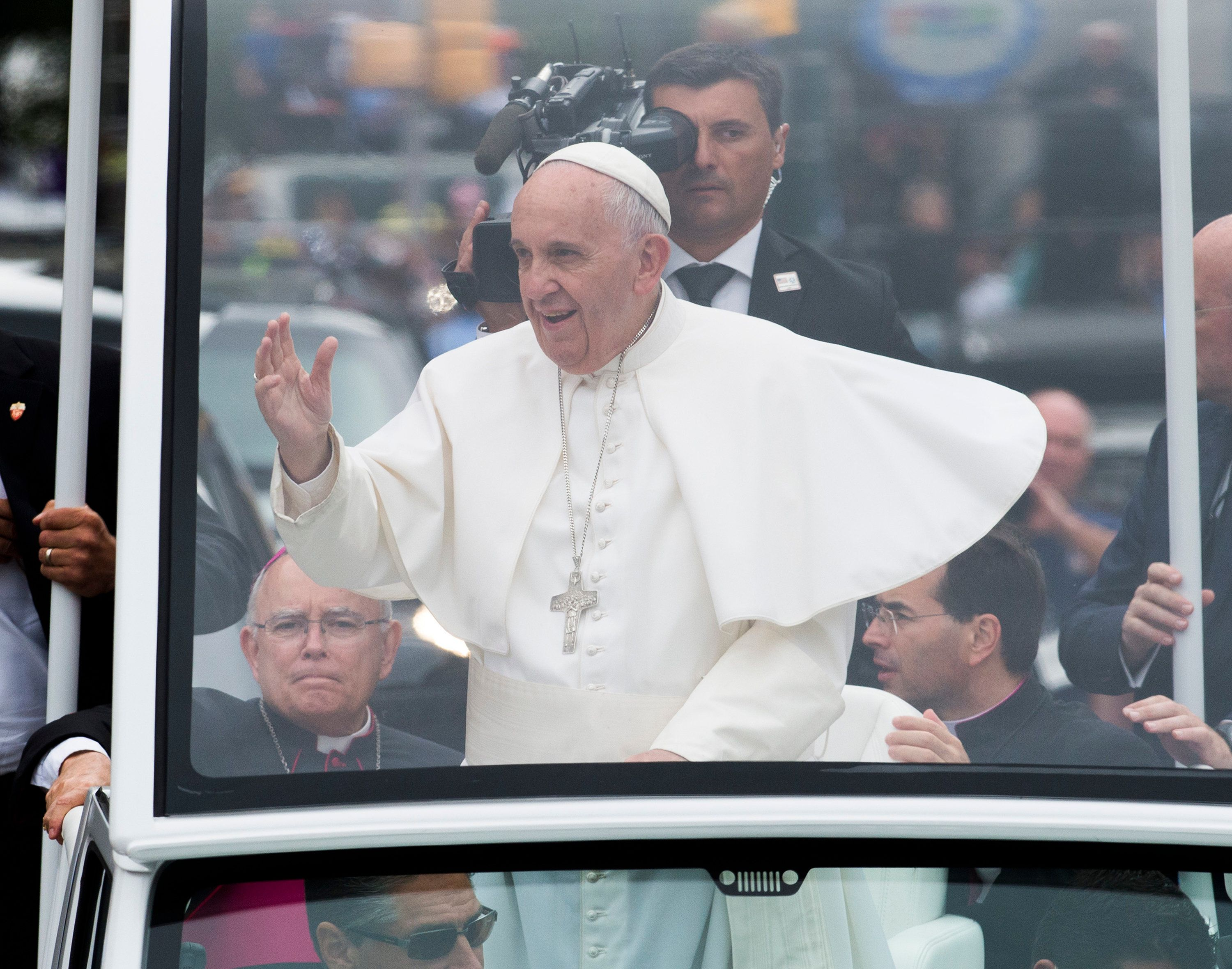 Pope Francis waves to pilgrims on the Benjamin Franklin Parkway in Philadelphia on Sunday, Sept. 27, 2015.