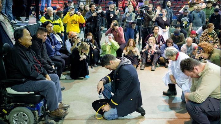 """<p>Lt. Wesley Clark Jr. kneels in front of Chief Leonard Crow Dog during the """"Forgiveness Ceremony.""""</p>"""