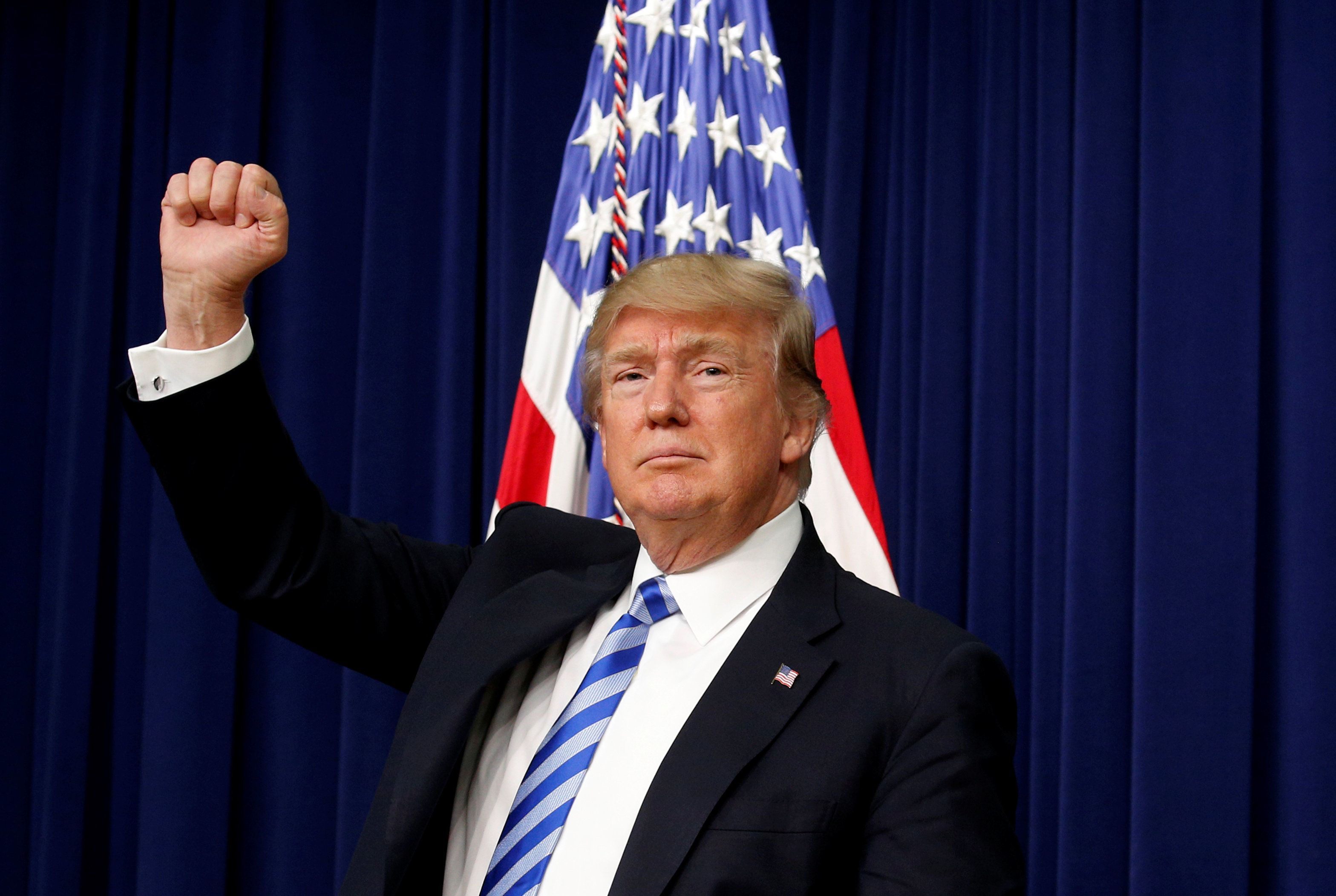 U.S. President Donald Trump pumps his fist as he departs after attending a CEO town hall on the American business climate at the Eisenhower Executive Office Building in Washington, U.S., April 4, 2017. REUTERS/Kevin Lamarque