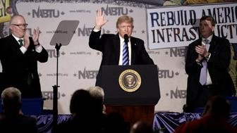 U.S. President Donald Trump, center, waves to attendees while on stage during the 2017 North America's Building Trades Unions National Legislative Conference in Washington, D.C., U.S., on Tuesday, April 4, 2017. Trade has emerged as one of the most contentious issues between the new U.S. administration and the rest of the world. Photographer: Olivier Douliery/Bloomberg via Getty Images