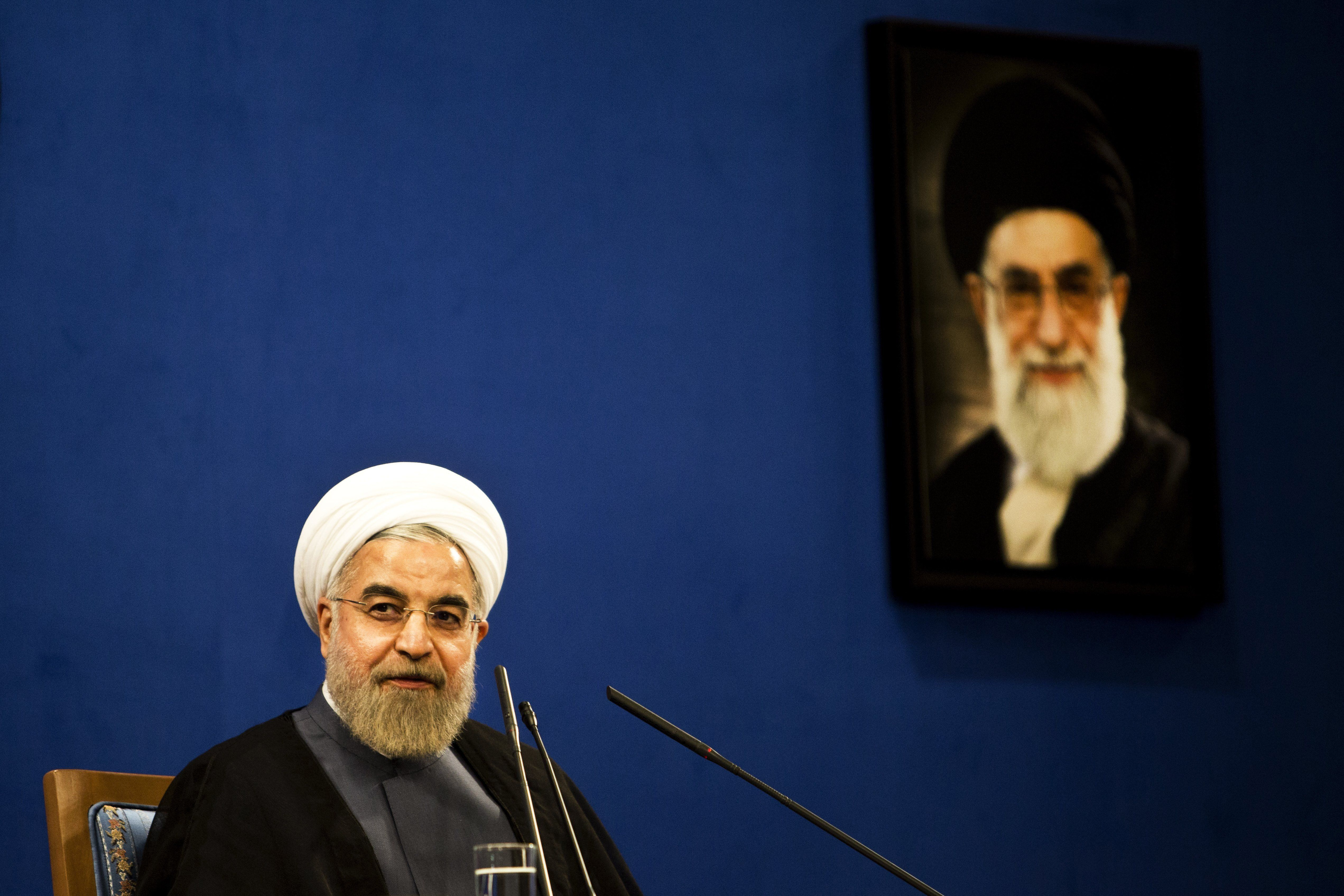 Iranian President Hassan Rouhani listens, sitting next to a portrait of supreme leader Ayatollah Ali Khamenei (R), during a press conference in Tehran on June 13, 2015. There are still 'many differences over details' of a nuclear deal Iran and world powers are trying to conclude by June 30, Iranian President Hassan Rouhani said.  AFP PHOTO / BEHROUZ MEHRI        (Photo credit should read BEHROUZ MEHRI/AFP/Getty Images)