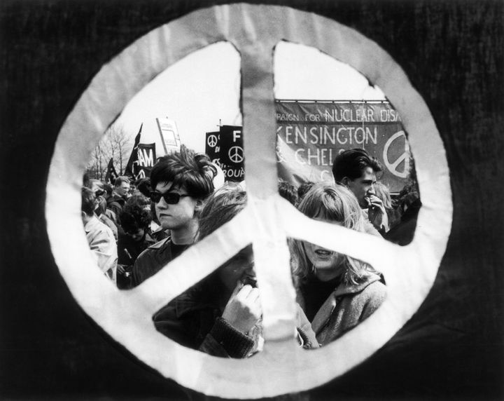 During a 1963 anti-nuclear demonstration from Aldermaston to London, a peace symbol frames the marchers and their banner