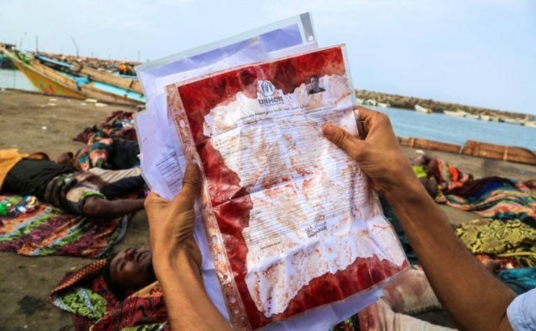 A man holds the UNHCR temporary registration document covered in blood from a refugee killed off the coast of Yemen on March 17 2016