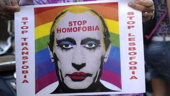 A demonstrator holds a poster depicting Russian President Vladimir Putin with make-up as he protests against homophobia and repression against gays in Russia, outside the Ministry of Foreign Affairs and Cooperation in Madrid on  September 3, 2013.  About 300 gay rights activists rallied in Madrid today as part of an international protest against hotly disputed Russian laws cracking down on homosexual behaviour.  AFP PHOTO/ CURTO DE LA TORRE        (Photo credit should read CURTO DE LA TORRE/AFP/Getty Images)