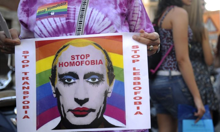 A demonstrator holds a poster depicting Russian President Vladimir Putin with makeup outside the Ministry of Foreign Affairs