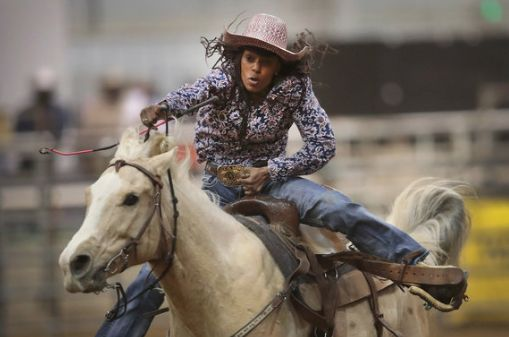 A cowgirl participates in the barrel race competition.