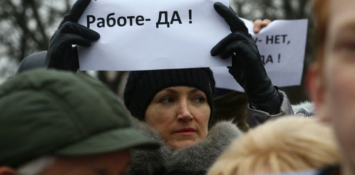 """A woman holds a placard reading """"No to decree, yes to work!"""" in the town of Bobruisk in Belarus on March 12 2017."""