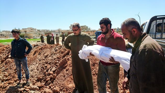 Syrians bury the bodies of victims of a a suspected toxic gas attack in Khan Sheikhun, a nearby rebel-held...