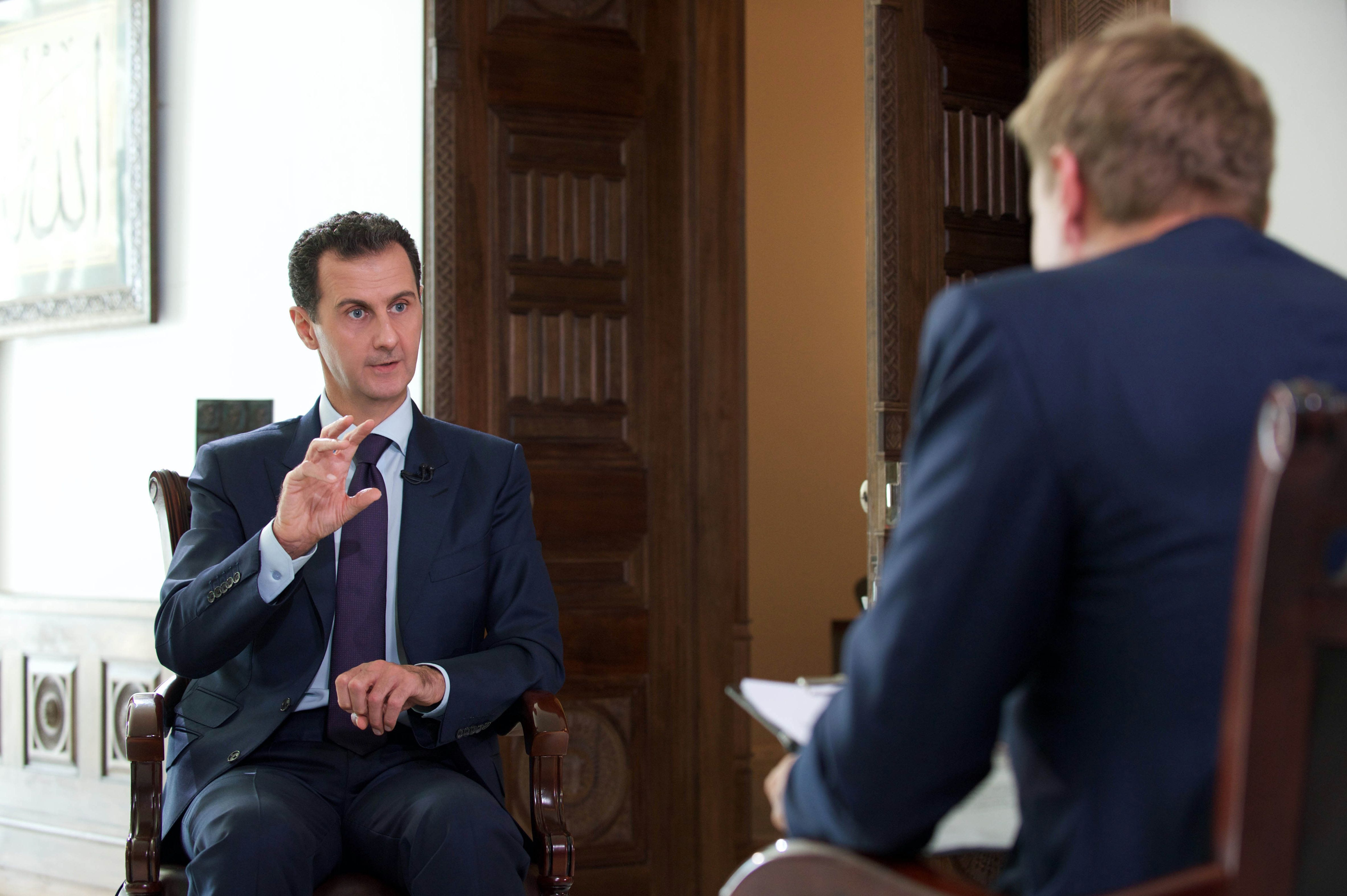 A handout picture released by the official Syrian Arab News Agency (SANA) on October 6, 2016  shows Syrian President Bashar al-Assad (L) speaking during an interview with Denmark's TV2 channel. / AFP / SANA / -        (Photo credit should read -/AFP/Getty Images)