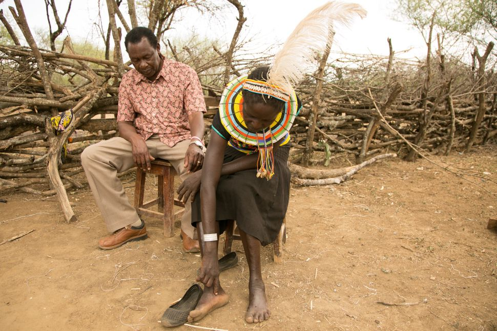 Cheposait Adomo, seated with Dr. Michael Makari, head of Kacheliba hospital in Kenya's West Pokot, describes how she was bitt