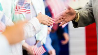 Unidentifiable man is politician at town hall meeting or political event. He is shaking hands with people who are lined up waving American flags.