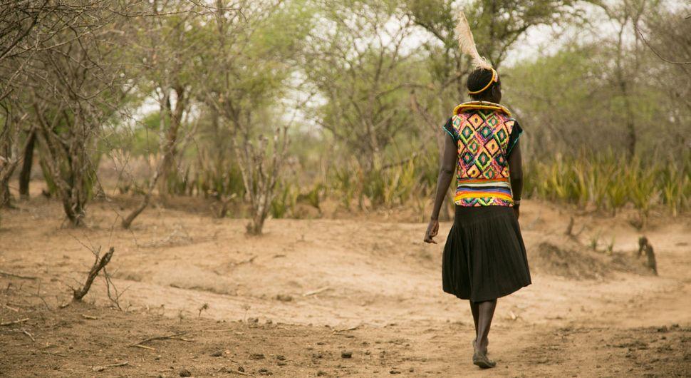 Cheposait Adomo walks in the bush in Kenya's West Pokot near where she was bitten repeatedly by a snake.
