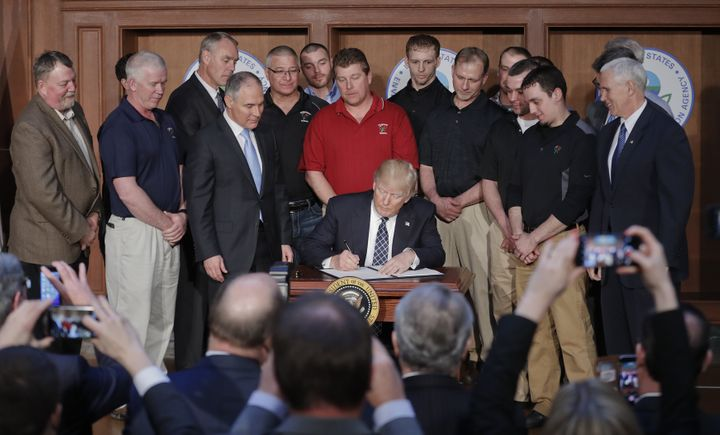 President Donald Trump signs an executive order on March 28 at the Environmental Protection Agency, aiming to unravel former