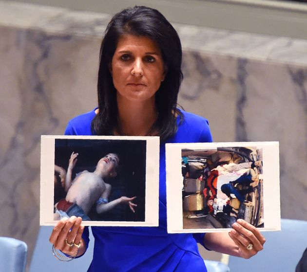 U.N. Ambassador Nikki Haley holding photos of the victims of a chemical weapons attack in Syria, urging...
