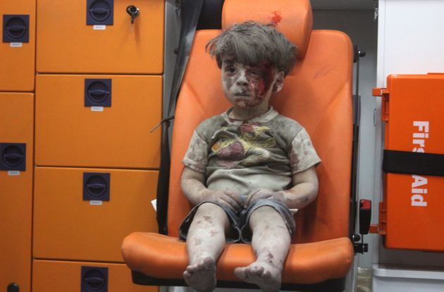 Omran Daqneesh, 5, sits alone in the back of the ambulance after beinginjured during anair...