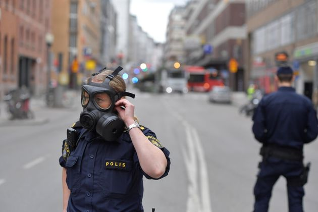 Police officers wear gas masks as they stand guard near the shopping