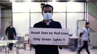 A medical staff at Damascus Countryside Specialised Hospital holds a placard condemning a suspected chemical weapons attack on the Syrian town of Khan Sheikhun, during a gathering to show solidarity with the victims in the rebel-held Douma on the outskirts of Damascus on April 6, 2017. US forces fired a barrage of cruise missiles at a Syrian airbase on April 7 in response to what President Donald Trump called a 'barbaric' chemical attack he blamed on the Damascus regime. Syria's regime has denied any use of chemical weapons and state media on Friday described the US strike -- which was reported to have pulverised the base and killed at least four servicemen -- as an 'act of aggression'. / AFP PHOTO / Sameer Al-Doumy        (Photo credit should read SAMEER AL-DOUMY/AFP/Getty Images)