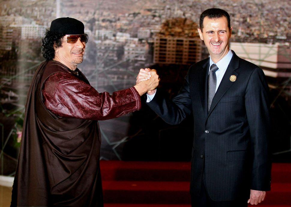 Syrian President Bashar Assad joins hands with then Libyan leader Muammar Gaddafi. Damascus, Syria. March 29, 2008.