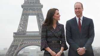 Britain's Prince William, the Duke of Cambridge, and his wife Kate, the Duchess of Cambridge, pose for photographers with the Eiffel tower in background after being welcomed by school children and students from the British Council's Somme project at the Trocadero square, in Paris, France, March 18, 2017. REUTERS/Michel Euler/Pool
