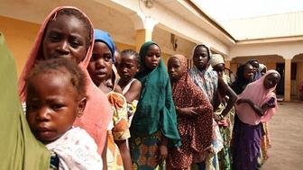 Women and girls rescued from Boko Haram pictured here lining up to collect donated clothes at a refugee camp in Yola are sometimes subjected to rejection by their families and verbal abuse by other female former captives