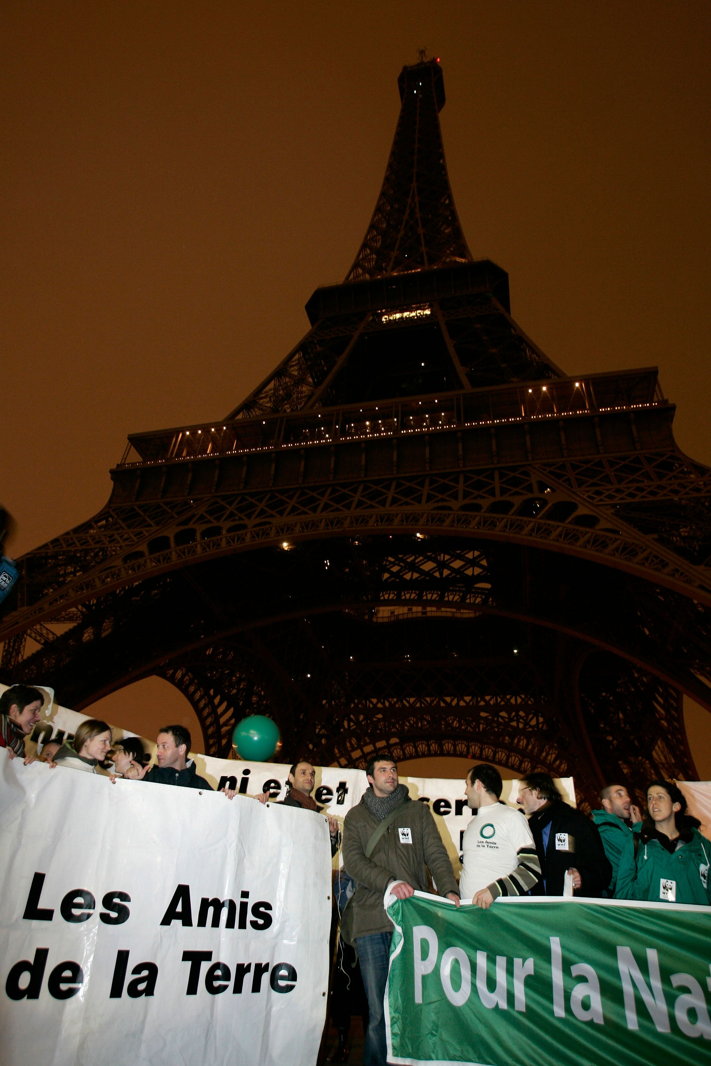 "People hold banners which read, ""Friends of the Earth"" (L) and ""For Nature"" (R) while gathering under a darkened Eiffel Tower as environmentalist campaigners in France urge the country to stop using electricity for 5 minutes between 7:55 and 8:00 p.m. to coincide the U.N. climate talks in Paris, February 1, 2007.    REUTERS/Benoit Tessier (FRANCE)"
