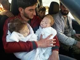 a father cradles his twins, murdered by the Assad regime with Sarin gas