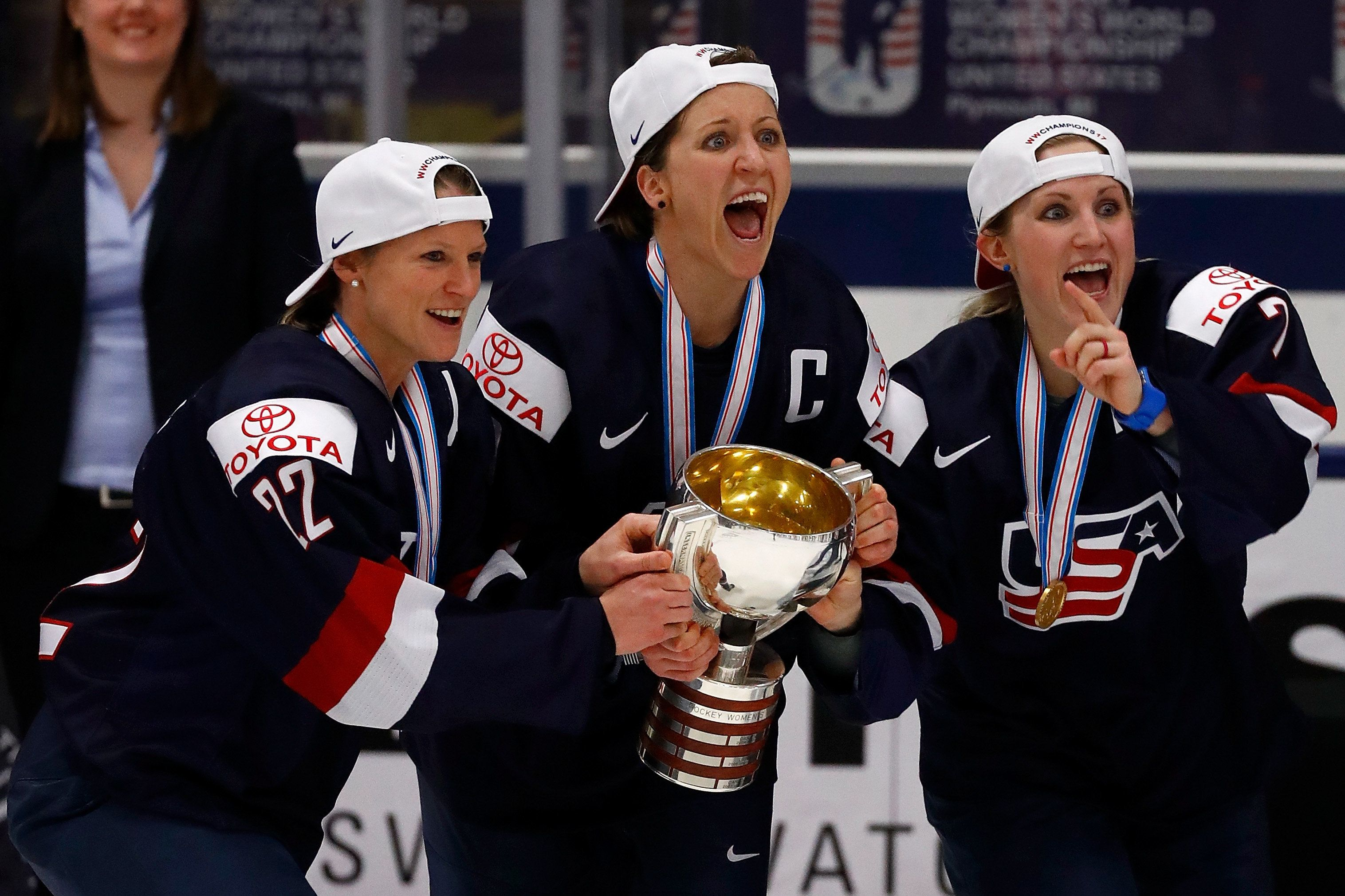 PLYMOUTH, MI - APRIL 07: Kacey Bellamy #22, Meghan Duggan #10 and Monique Lamoureux #7 of the United States react after receiving the championship trophy for beating Canada 3-2 in overtime in the gold medal game at the 2017 IIHF Woman's World Championships at USA Hockey Arena on April 7, 2017 in Plymouth, Michigan. (Photo by Gregory Shamus/Getty Images)