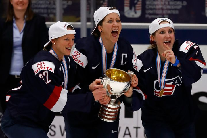 Kacey Bellamy, left, Meghan Duggan and Monique Lamoureux grab on to the championship trophy afterbeating Canada, 3-2, i