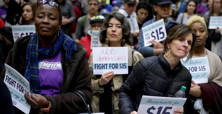 Women take part in a National Day of Action 15 dollar per hour minimum wage protest at the Massachusetts State House in