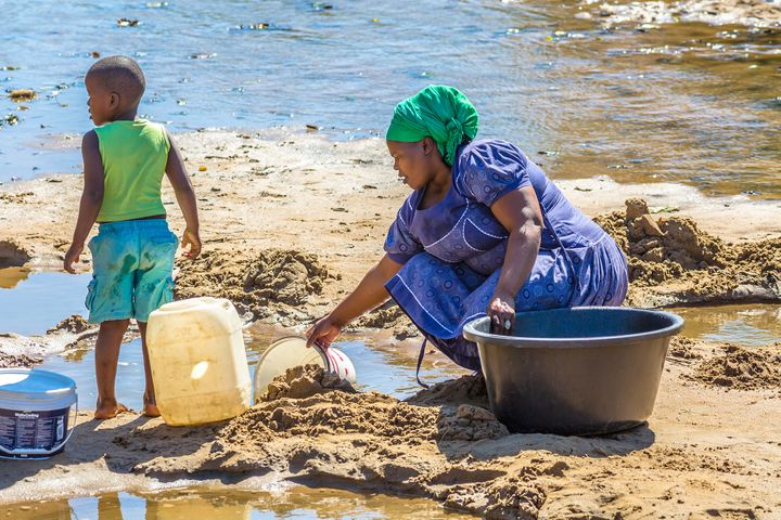 South Africa - August 24, 2014: African woman with child collecting water from the river on the road leading to local Game Re