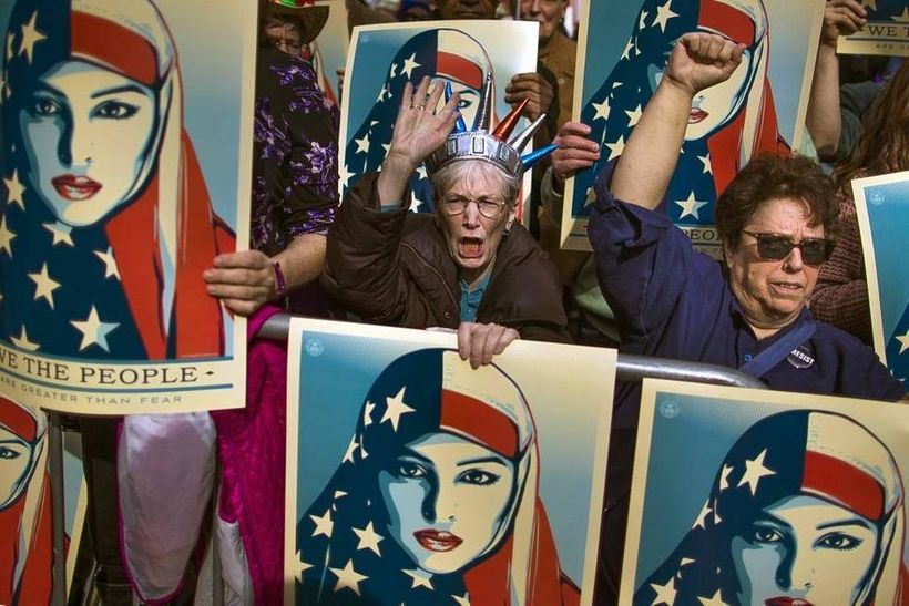 People carry posters during a rally against President Donald Trump's executive order banning travel from seven Muslim-majori