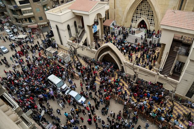 People gather in front of the Saint George church after a bombing struck inside the church in the Nile...