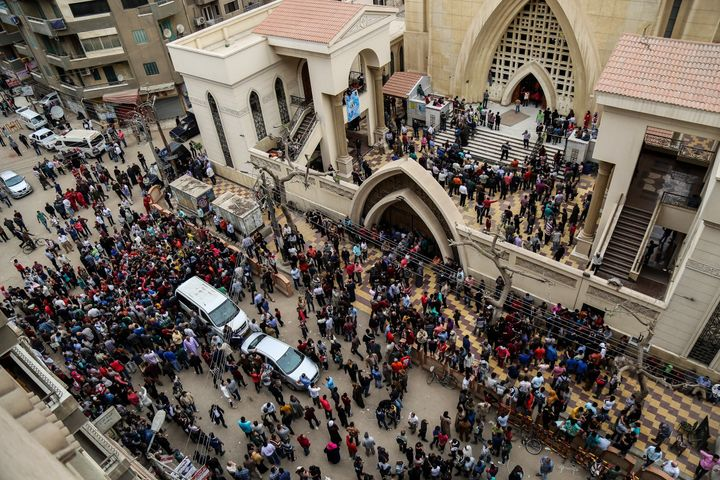 People gather in front of the Saint George church after a bombing struck inside the church in the Nile Delta city of Tanta, E