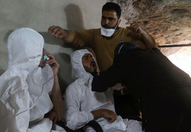 A man breathes through an oxygen mask as another one receives treatments, after what rescue workers described...