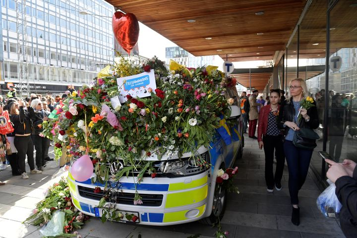 A police vehicle is seen adorned with a mound of flowers and balloons following Friday's attack.
