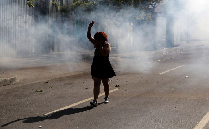 A woman walks away from tear gas during a rally in Caracas.