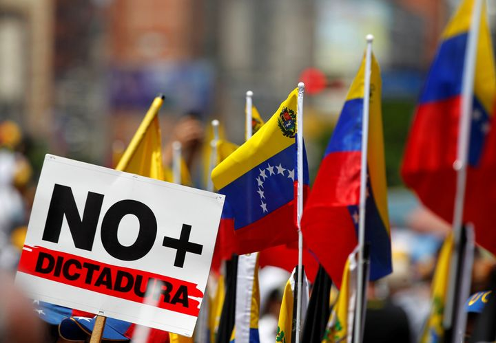 "A signs that reads ""No more dictatorship"" and Venezuelan flags are seen during an opposition rally in Caracas, Venezuela, Apr"