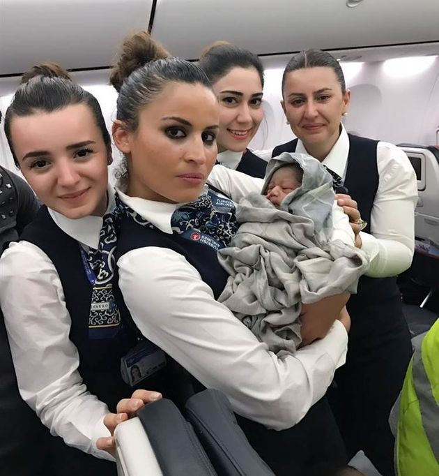 Four members of Turkish Airlines staff are seen welcoming an unexpected passenger following a mid-flight