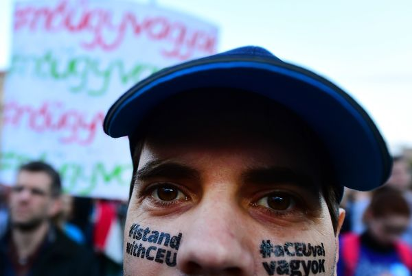 "A man protests with the slogan ""I stand with CEU"" on his face."