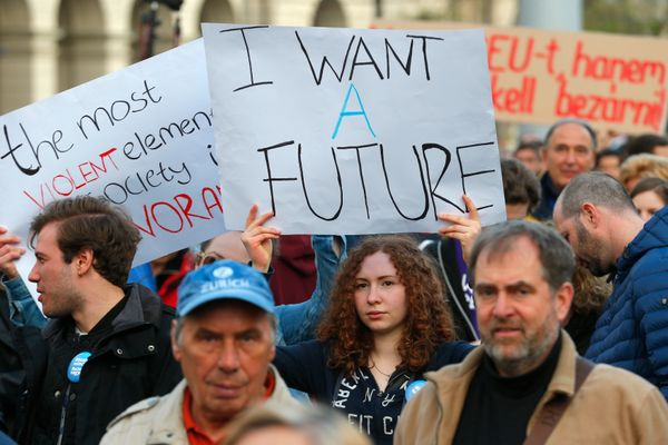"A protester holds up a sign reading ""I want a future."""