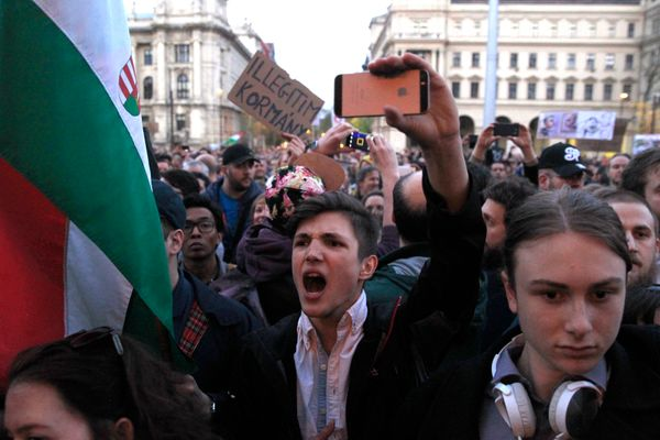 A protester yells while protesting on the streets of Budapest.