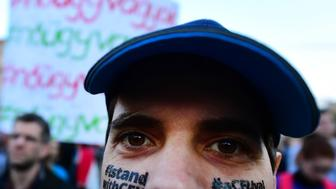 A man protests with a slogan on his face 'I stands with CEU' as students and teachers of the Central European University protest with their sympathizers in front on Parliament in Budapest on April 9, 2017.  Hungarian lawmakers approved legislation that could force the closure of a prestigious Budapest university founded by US billionaire investor George Soros, sparking fresh protests. The English-language Central European University (CEU), set up in 1991 after the fall of communism, has long been seen as a hostile bastion of liberalism by Prime Minister Viktor Orban's government.   / AFP PHOTO / ATTILA KISBENEDEK        (Photo credit should read ATTILA KISBENEDEK/AFP/Getty Images)