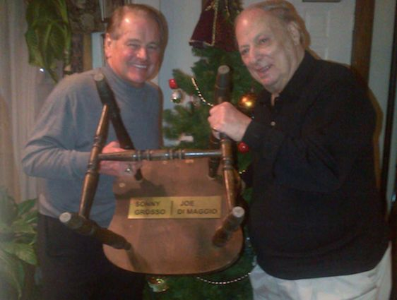 <strong><em>NY Rangers legend Rod Gilbert and Det. Grosso hold up the Manducati Restaurant's chair that the Yankee Clipper sa