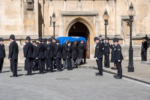 PC Keith Palmer's coffin passes a police guard of honour as it arrives at Westminster