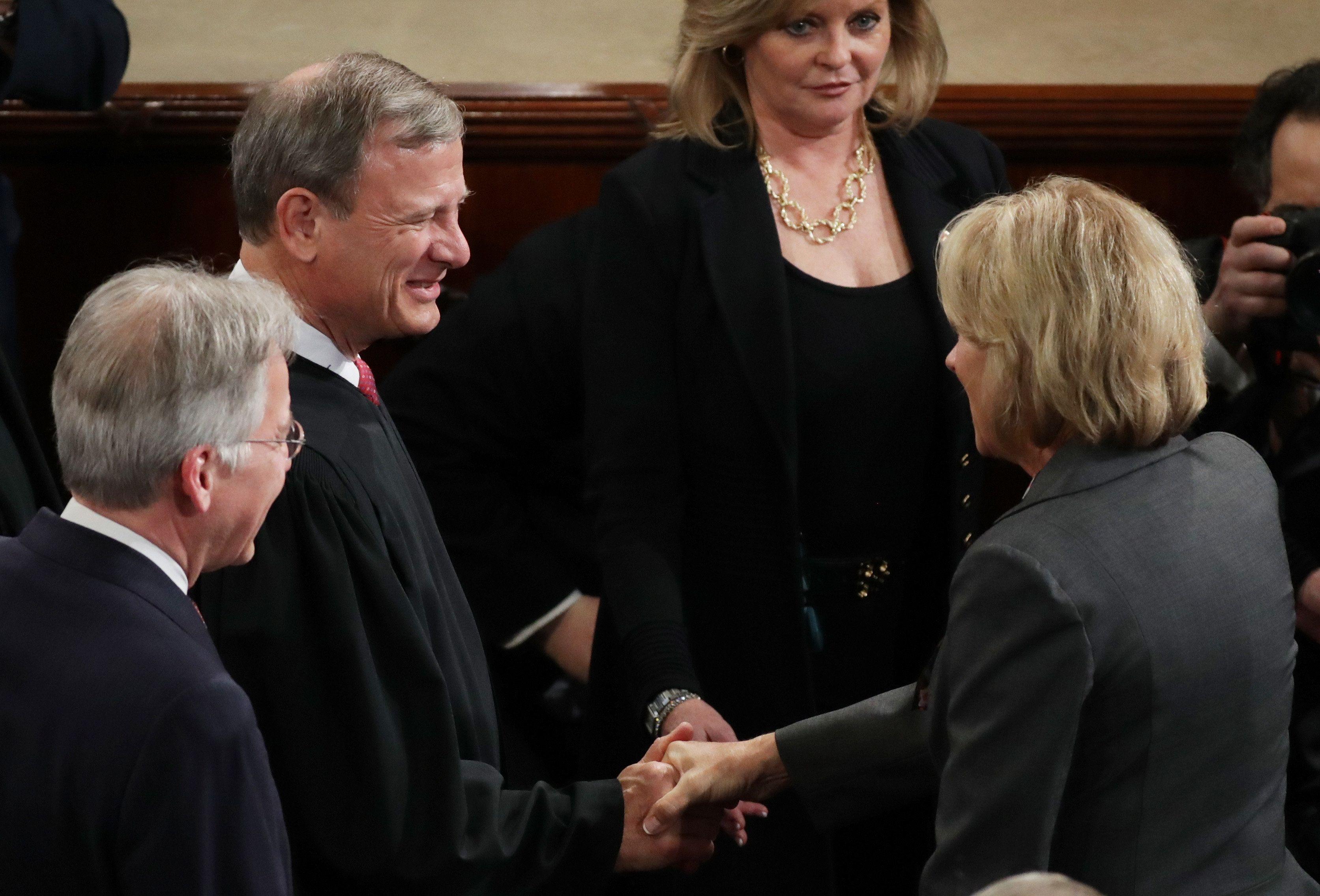 Supreme Court Chief Justice John Roberts shakes hands with Education Secretary Betsy DeVos as they arrive to President T