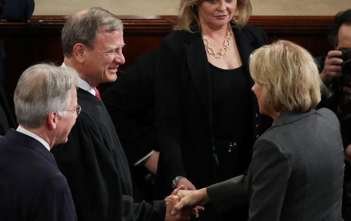 Supreme Court Chief Justice John Roberts shakes hands with Education Secretary Betsy DeVos as they arrive to PresidentT