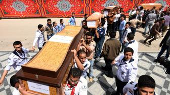 Christian scouts carry the coffins of victims of the blast at the Coptic Christian Saint Mark's church in Alexandria the previous day during a funeral procession at the Monastery of Marmina in the city of Borg El-Arab, east of the northern port city on April 10, 2017. Egypt prepared to impose a state of emergency after jihadist bombings killed dozens at two churches in the deadliest attacks in recent memory on the country's Coptic Christian minority. / AFP PHOTO / MOHAMED EL-SHAHED        (Photo credit should read MOHAMED EL-SHAHED/AFP/Getty Images)