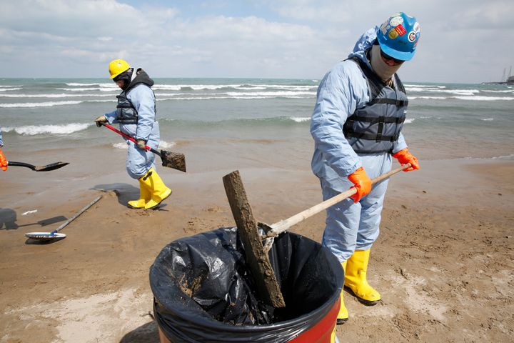 Oil spill response contractors clean up crude oil on a beach after a BP oil spill on Lake Michigan in Whiting, Indiana March