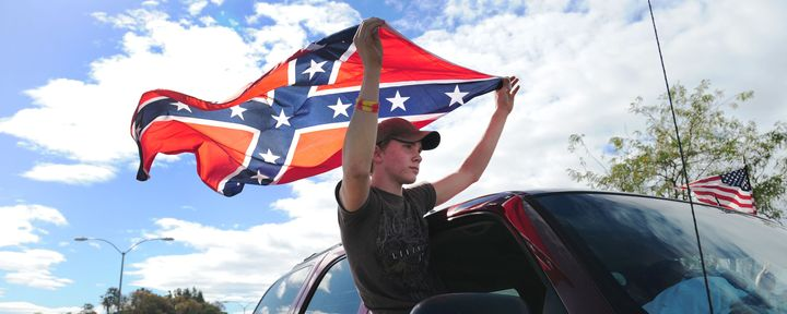 A protester with a Confederate flag drives past other demonstrators in Roseburg, Oregon, in October 2015. President Barack Obama was visiting a week after the mass shooting at Umpqua Community College.