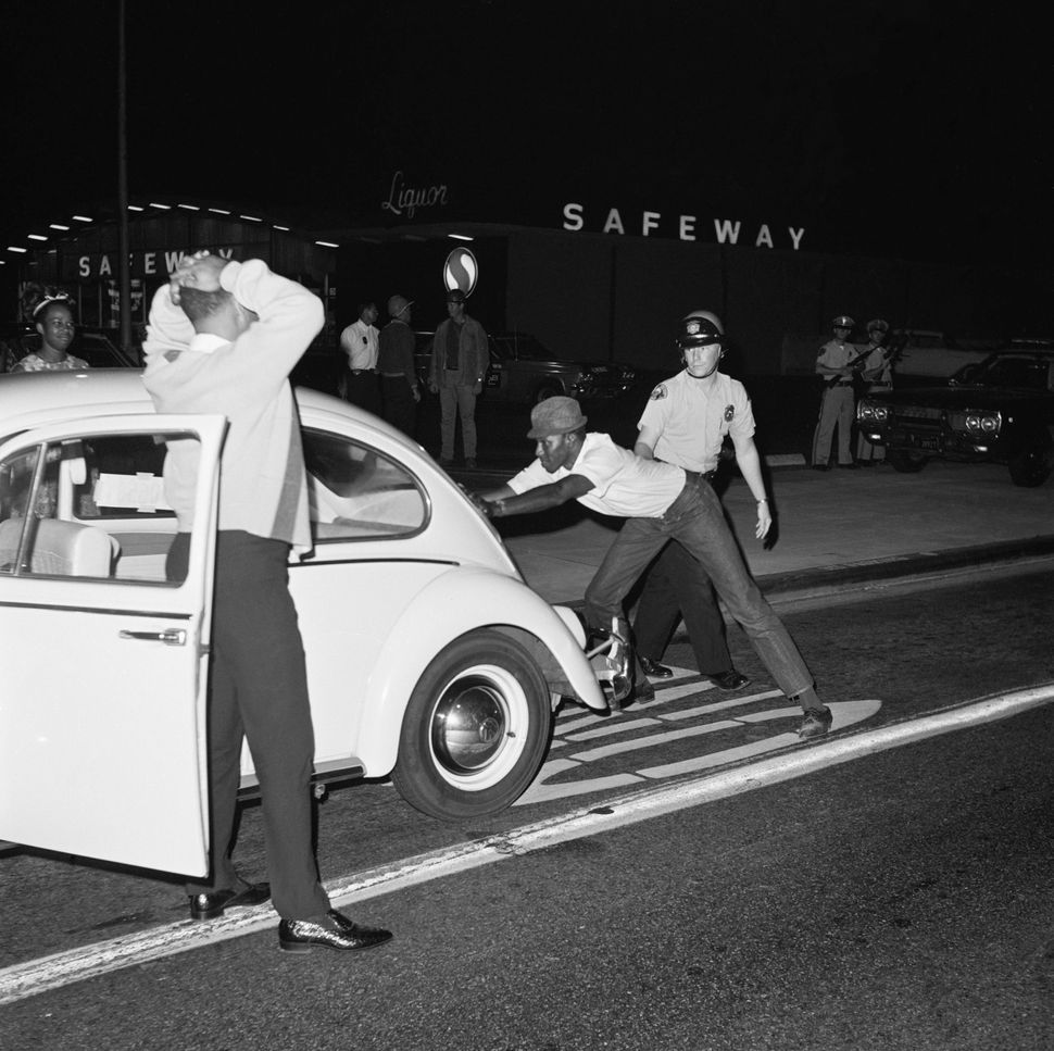 A Long Beach police officer searches black drivers and passengers for weapons at a checkpoint during the Watts Rebellion in n